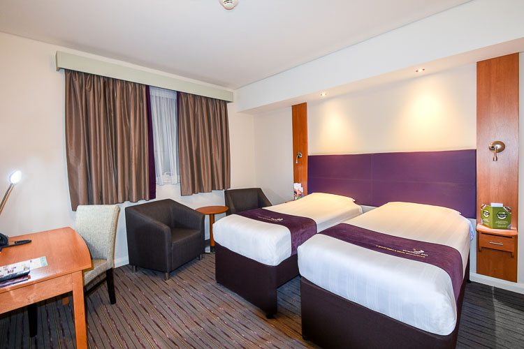 Twin beds with desk and seating area in hotel near Expo 2020 in Dubai Investments Park