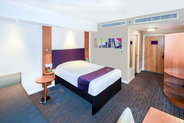 Double bedroom with sofa and ensuite bathroom in Premier Inn Dubai Investments Park hotel near Expo 2020