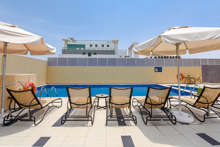 Free sunloungers at swimming pool in hotel Premier Inn Dubai Silicon Oasis