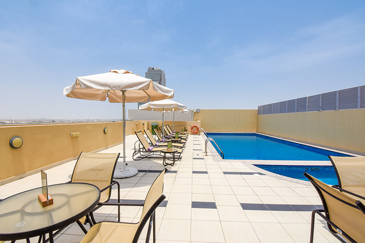 Poolside dining area at rooftop swimming pool in Dubai Silicon Oasis hotel