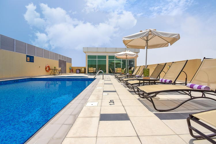 Rooftop swimming pool with towels and sun loungers in Silicon Oasis hotel in Dubai