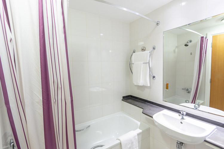 En-suite private bathroom with bath and shower at Premier Inn Abu Dhabi International Airport hotel