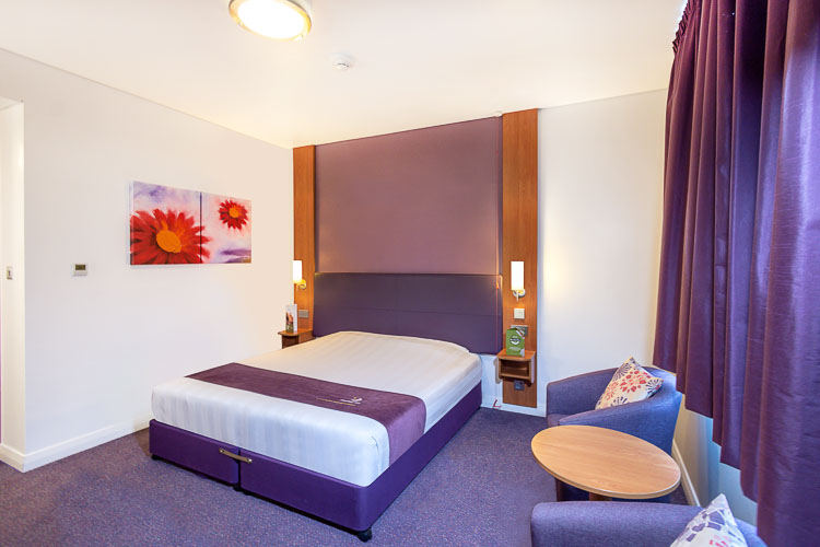 Double room with large bed and seating area at Premier Inn Abu Dhabi International Airport hotel
