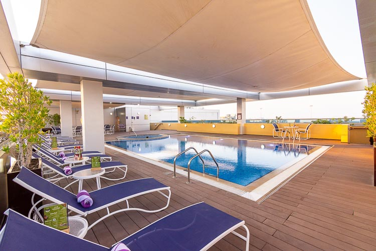 Free sun loungers at swimming pool with cover at Premier Inn Abu Dhabi International Airport hotel