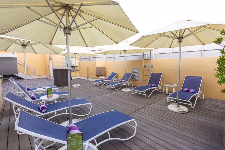 Sun terrace deck with free sun loungers and beds with umbrellas at Premier Inn Abu Dhabi International Airport hotel