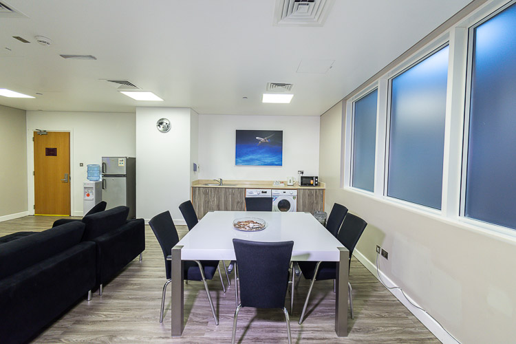 Table and chairs with self-service laundry in shared space for long stay guests ath the airport hotel in Abu Dhabi