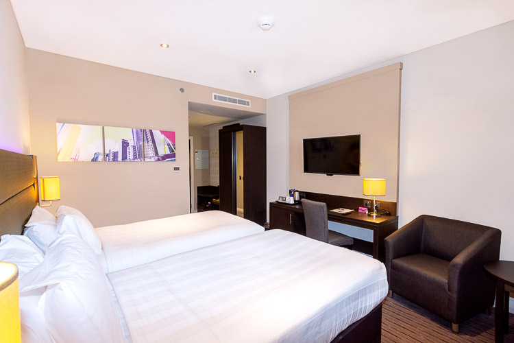 Twin bedroom with seating area and desk space in Dubai hotel