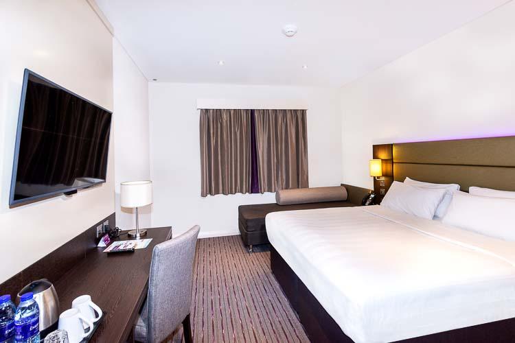 Large bed with sofa and Smart TV in Premier Inn Dubai Al Jaddaf hotel