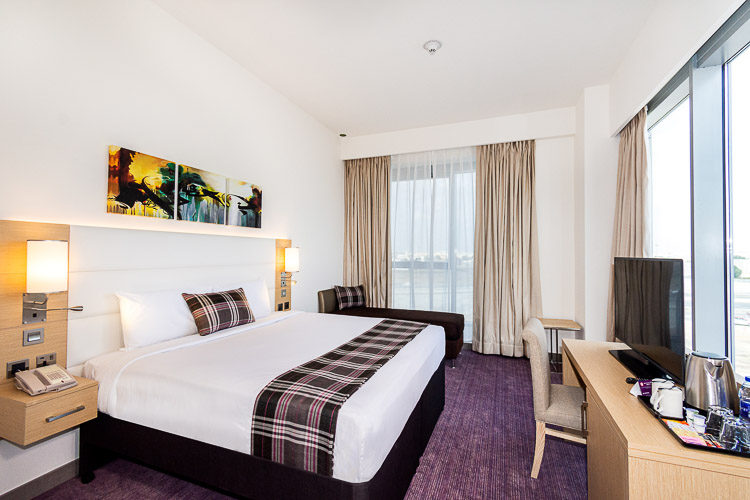 Hotel room in Dubai with double bed and sofa in a 3 star hotel near Dragon Mart