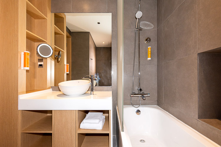 Ensuite bathroom with bath tub and shower in budget hotel in Dubai