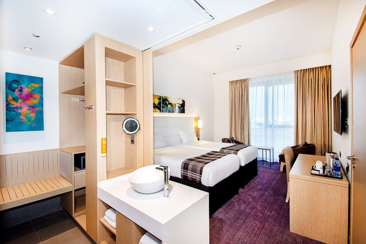 Twin bedroom with ensuite bathroom and wardrobe at budget hotel in Dubai
