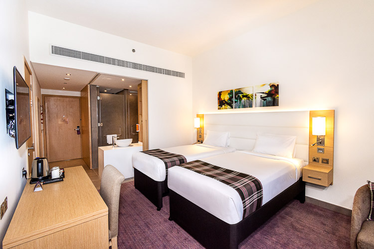 Twin bedroom with desk and seating area in a 3 star hotel in Dubai