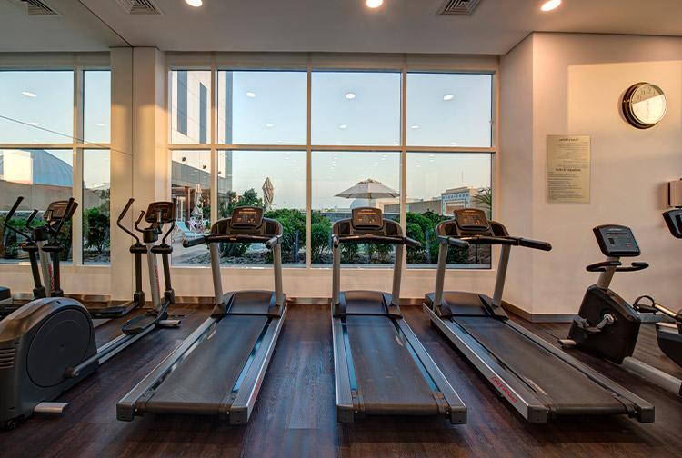 Running machines overlooking swimming pool at Ibn Battuta Hotel