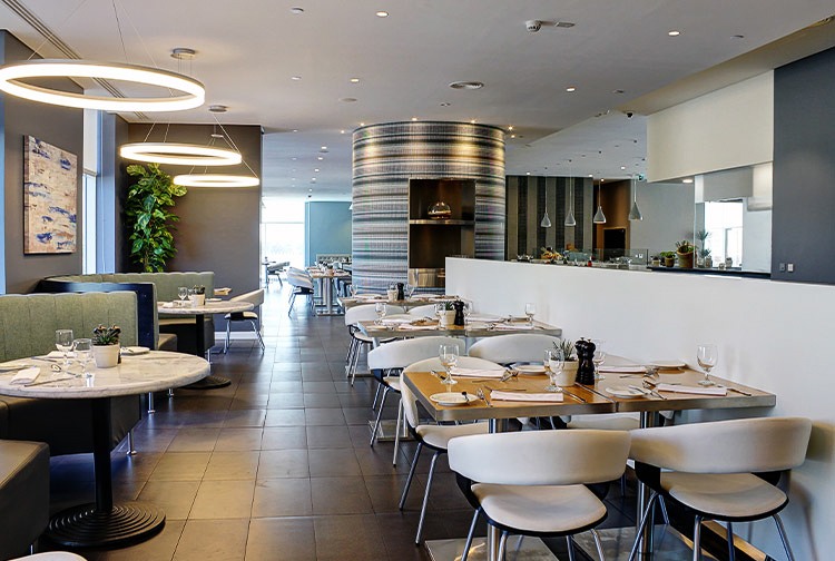 Table and booth seating available at Nuevo Restaurant in Premier Inn Ibn Battuta Mall hotel