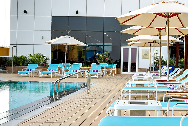 Swimming pool with terrace and sun loungers at Premier Inn hotel near Expo 2020