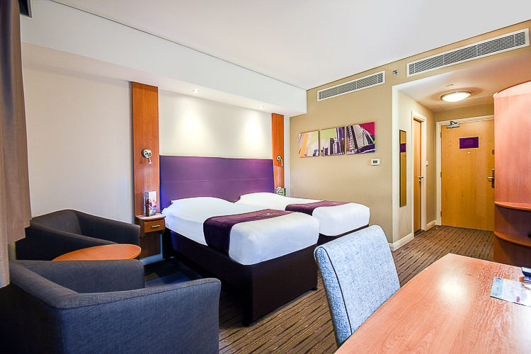 A twin room with two beds, en-suite bathroom and work space area at Premier Inn Dubai International Airport hotel