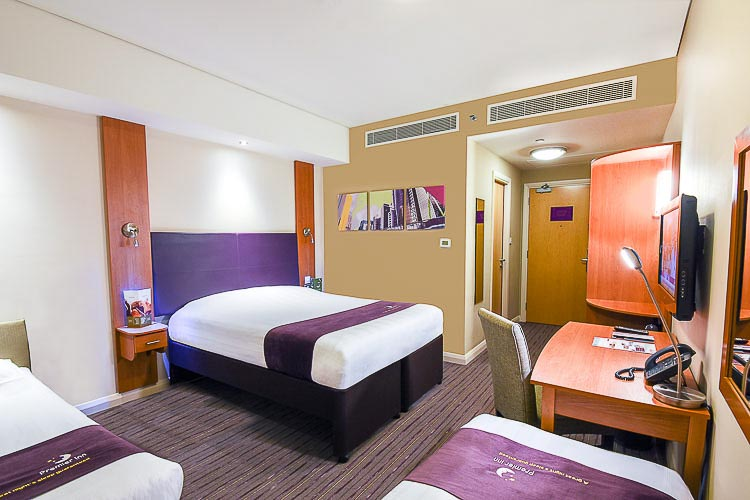 Family room with double bed and two single beds at Premier Inn Dubai International Airport hotel