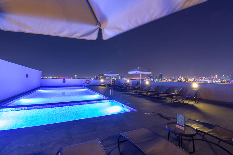 Swimming pool at night with lights and Dubai Airport views