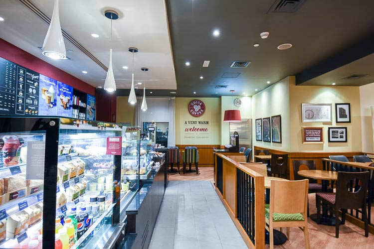 Light lunches and snacks at Costa Coffee shop with seating indoors for guests at Premier Inn Dubai International Airport hotel