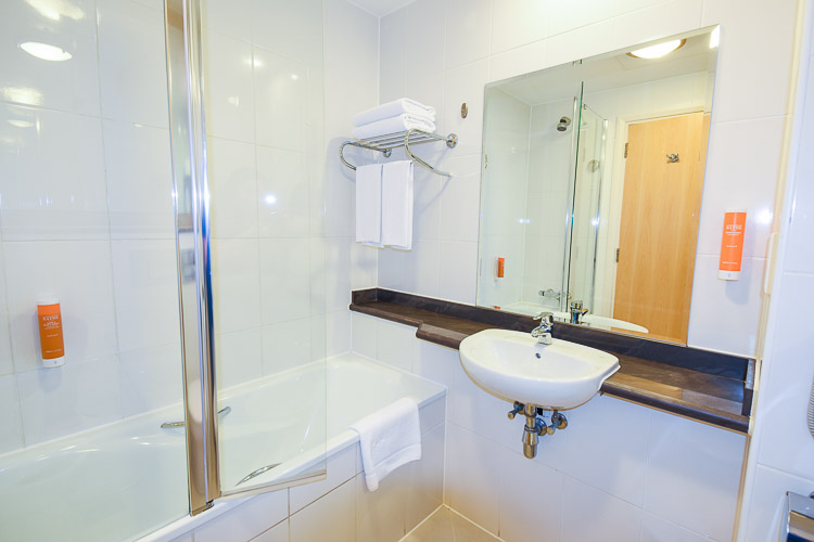 En-suite bathroom with bath and over-bath shower and glass shower screen.