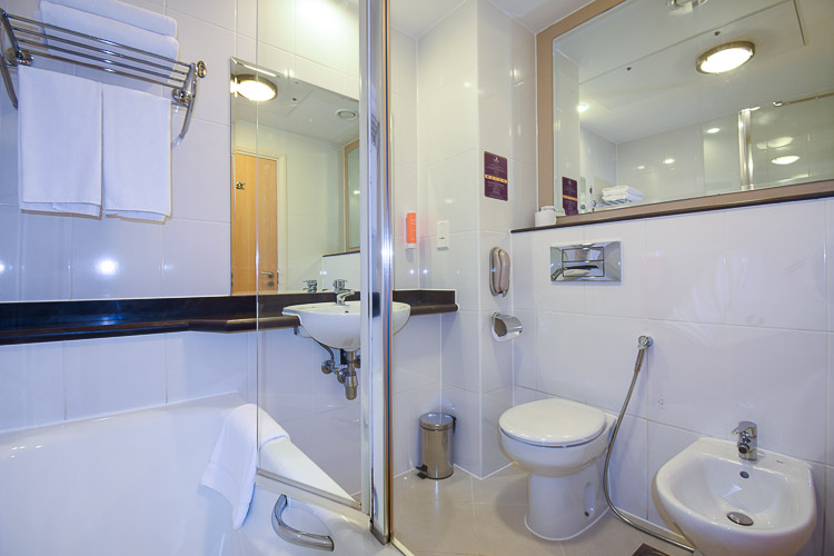 Bathroom with over-bath shower and bidet.