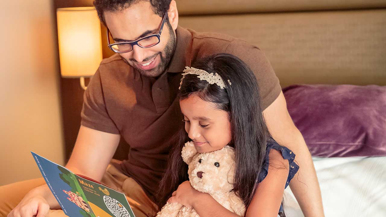 image of a dad reading a story to his daughter at premier inn hotel
